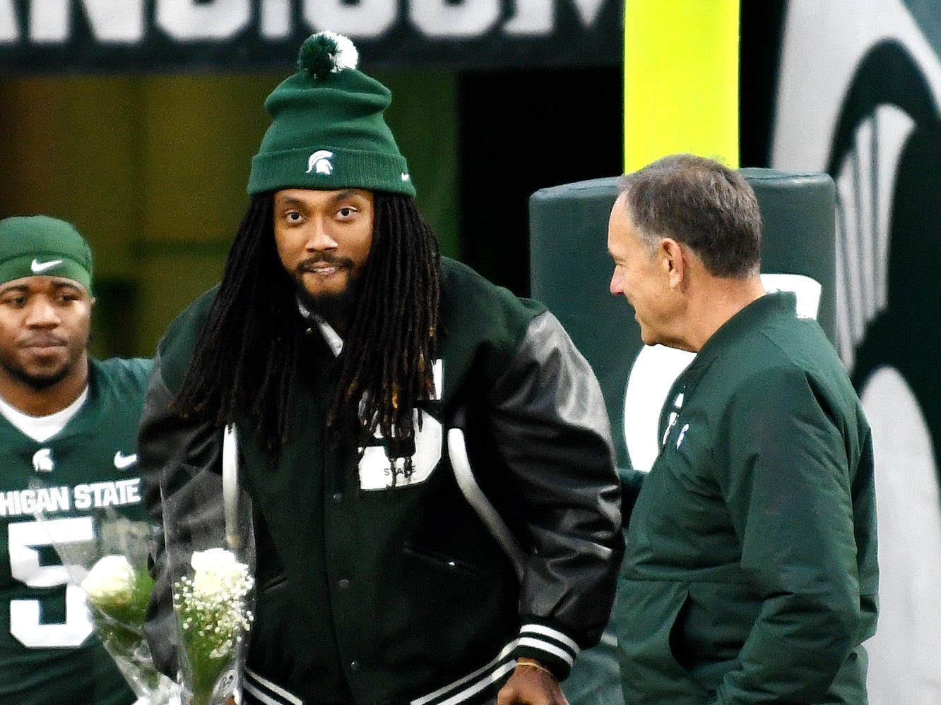 Michigan State senior wideout Felton Davis with head coach Mark Dantonio, as Davis is recognized during a ceremony before the game against Rutgers, Nov. 24, 2018, at Spartan Stadium in East Lansing.