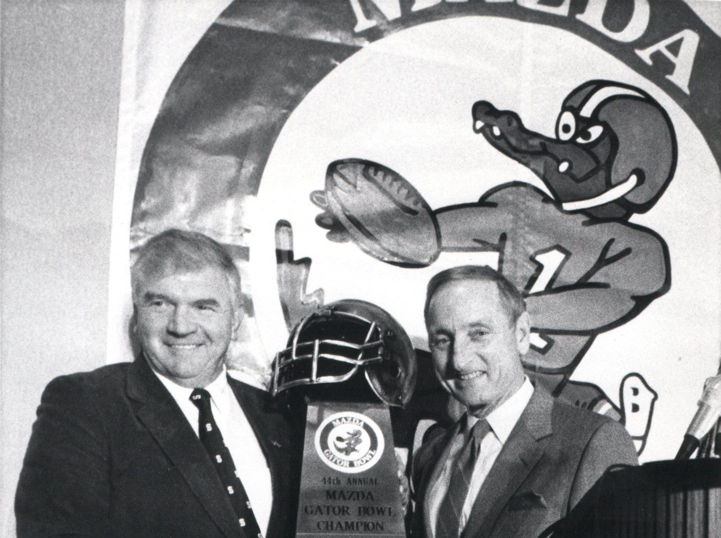 MSU head coach George Perles and Georgia head coach Vince Dooley pose with the Mazda Gator Bowl Trophy before a coaches luncheon at the downtown Sheraton in Jacksonville. Michigan Governor James Blanchard was also in attendance, Nov. 30, 1989.