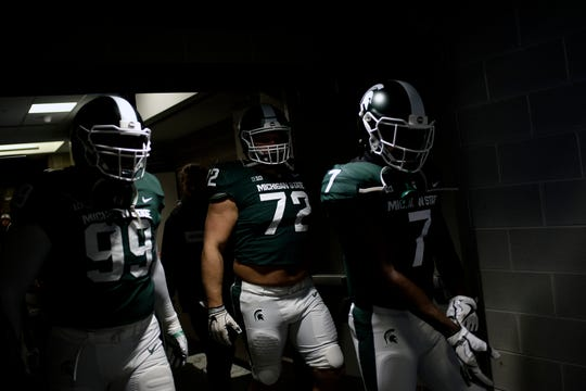 From left, Michigan State's Raequan Williams, Mike Panasiuk and Michael Dowell walk out of the locker room on their way to the field before the Spartans game against Purdue on Saturday, Oct. 27, 2018, in East Lansing.
