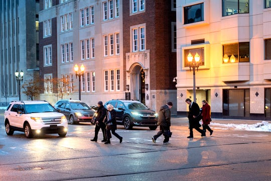 Pedestrians cross Ottawa Street at the Capitol Avenue intersection at the end of the work day on Thursday, Nov. 29, 2018, in downtown Lansing.