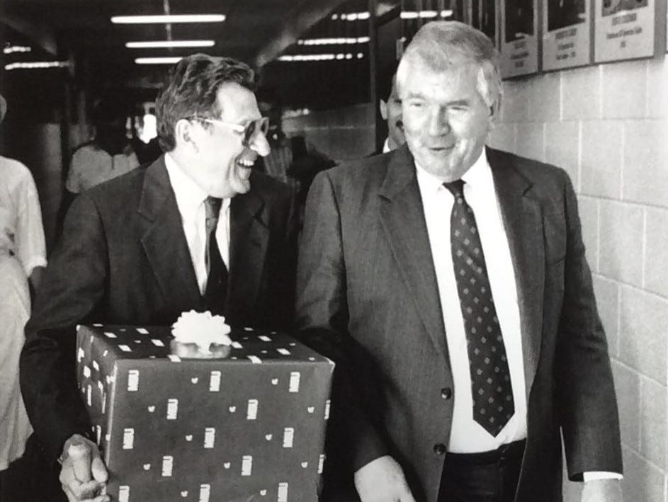 Penn State head football coach Joe Paterno playfully nudges MSU AD and head football coach George Perles with a gift from the athletic department as the two leave a press conference at the Duffy Daugherty football building. Perles hosted a series of press conferences for the Penn State coach as a welcome to the newest member of the Big Ten conference, undated photo.