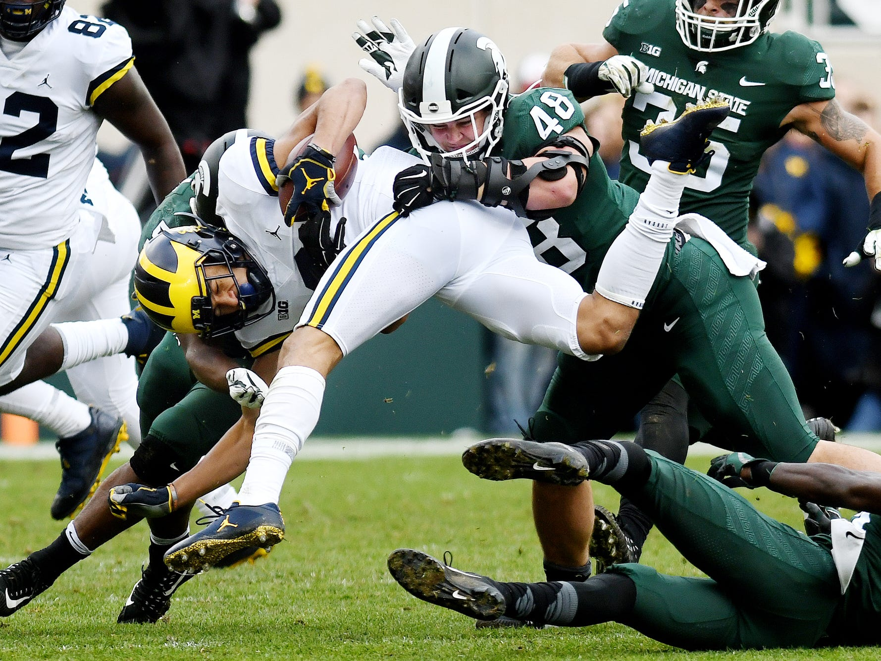 Michigan State's Kenny Willekes, right, tackles an airborne Michigan's Ronnie Bell during the second quarter on Saturday, Oct. 20, 2018, in East Lansing.