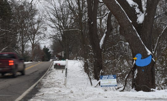 """A blue duck and signage seen outside a home on Clark Road in Bath Township indicate support of Robert Park's """"The Blue Loop"""" art installation."""