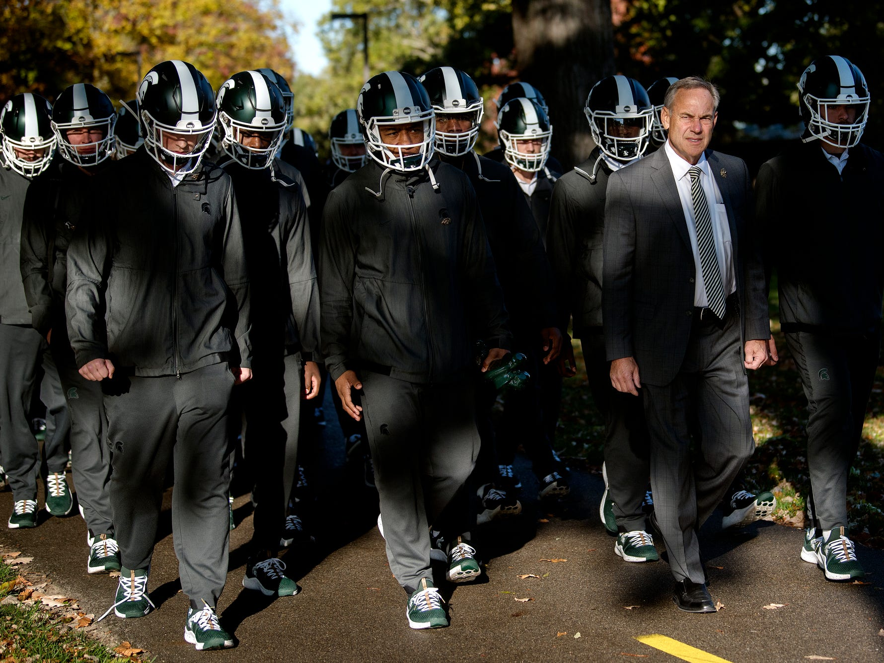 Michigan State head coach Mark Dantonio and the Spartans football team walk to Spartan Stadium before the game against Michigan on Saturday, Oct. 20, 2018, in East Lansing.