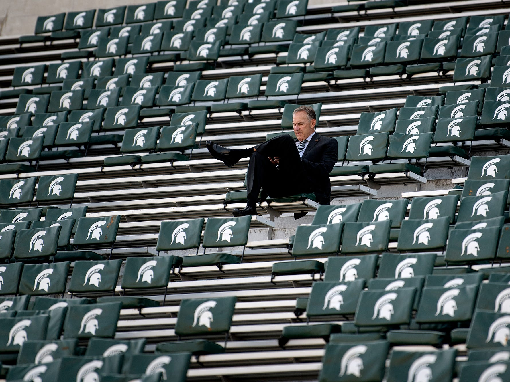 Michigan State's head coach Mark Dantonio sits alone in the stands before the Spartans' game against Utah State on Friday, Aug. 31, 2018, at Spartan Stadium in East Lansing.