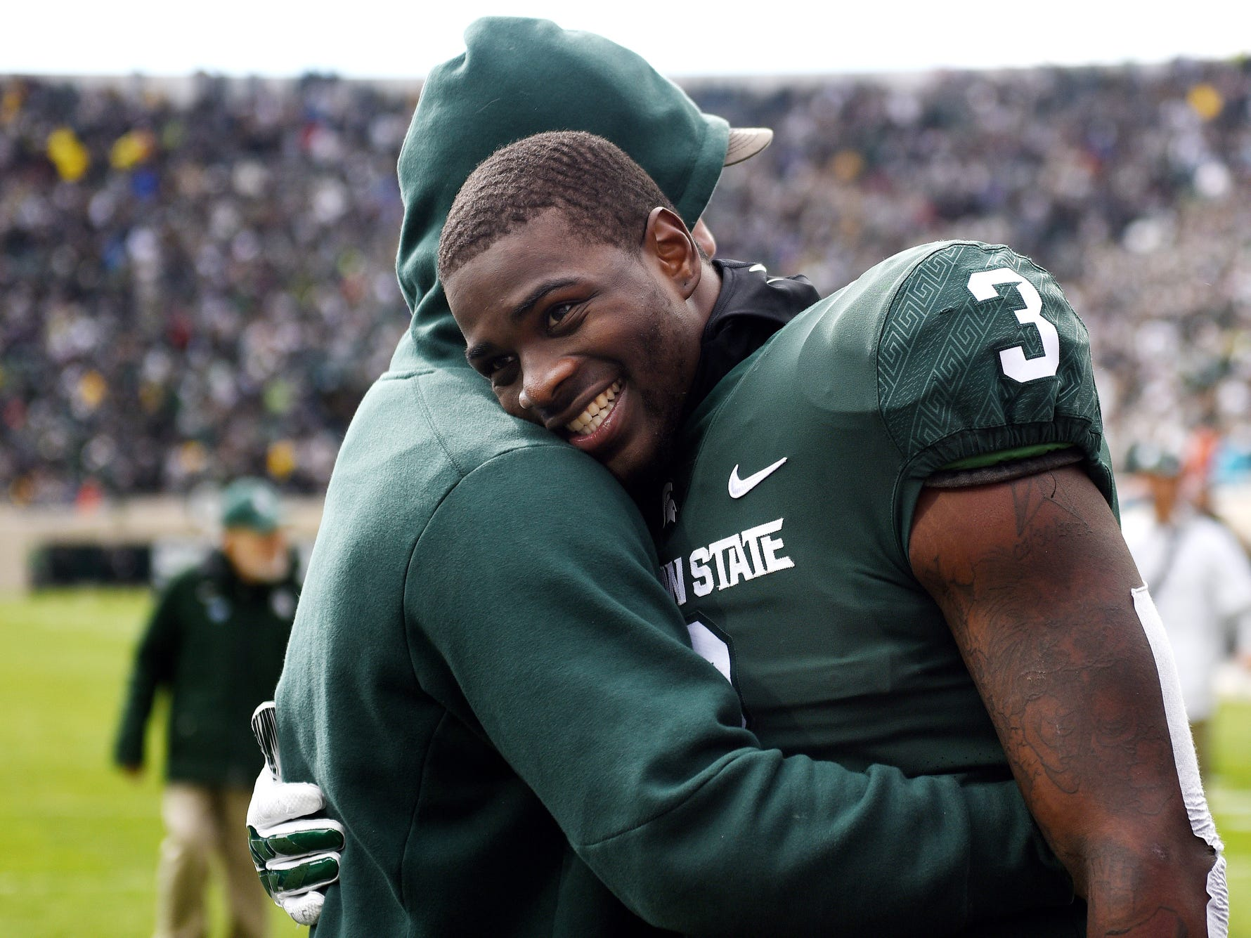 Michigan State's LJ Scott, right, hugs former Spartans linebacker Chris Frey while walking back to the locker room after the weather delay announcement in the first quarter on Saturday, Oct. 20, 2018, in East Lansing.