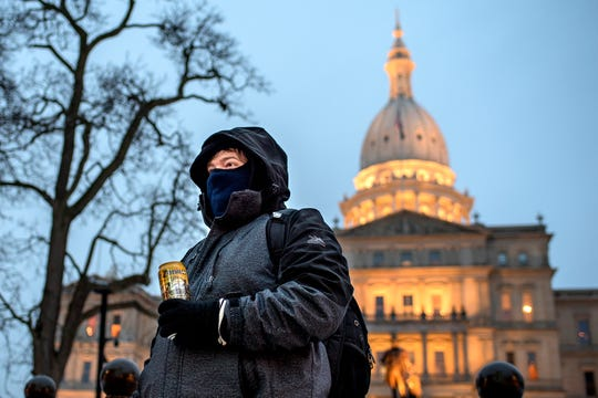 Jonathan Wild, of Grand Rapids, walks along Capitol Avenue to his parking garage after leaving work on Thursday, Nov. 29, 2018, in downtown Lansing.