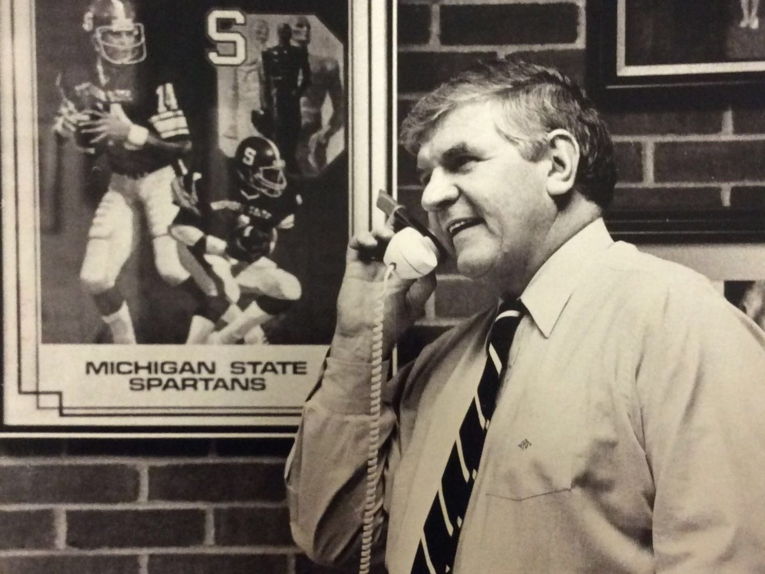 MSU football coach George Perles talks to recruit James Johnson on his football office phone, February 1987.