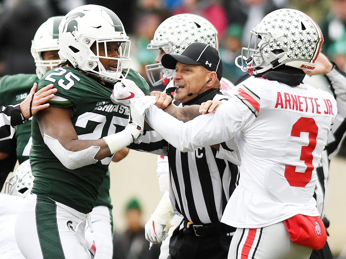 A ref breaks up a tussle between Michigan State's Darrell Stewart Jr., left, and Ohio State's Damon Arnette Jr. during the first quarter on Saturday, Nov. 10, 2018, in East Lansing.