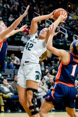 Michigan State's Kayla Belles, center, grabs a rebound between Virginia defenders during the fourth quarter on Wednesday, Nov. 28, 2018, at the Breslin Center in East Lansing. The Spartans won 91-66.