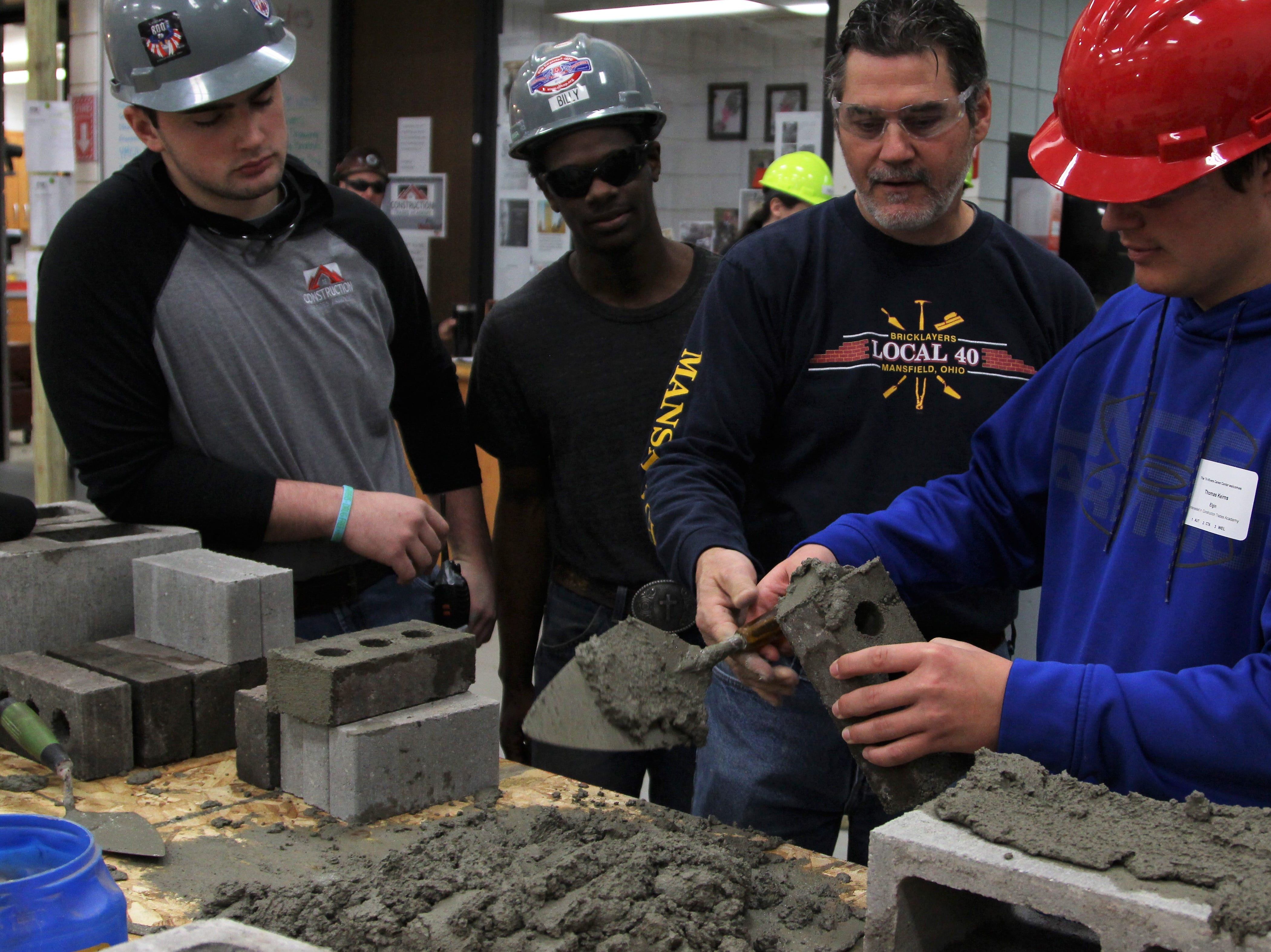 Matt McClester, a mason from Mansfield Local 40, helps Elgin freshman Thomas Keirns plaster a concrete brick. Union members and other professionals worked with potential students of the Construction Trades Academy at Tri-Rivers on Thursday. It was one of several work sessions scheduled throughout the day.
