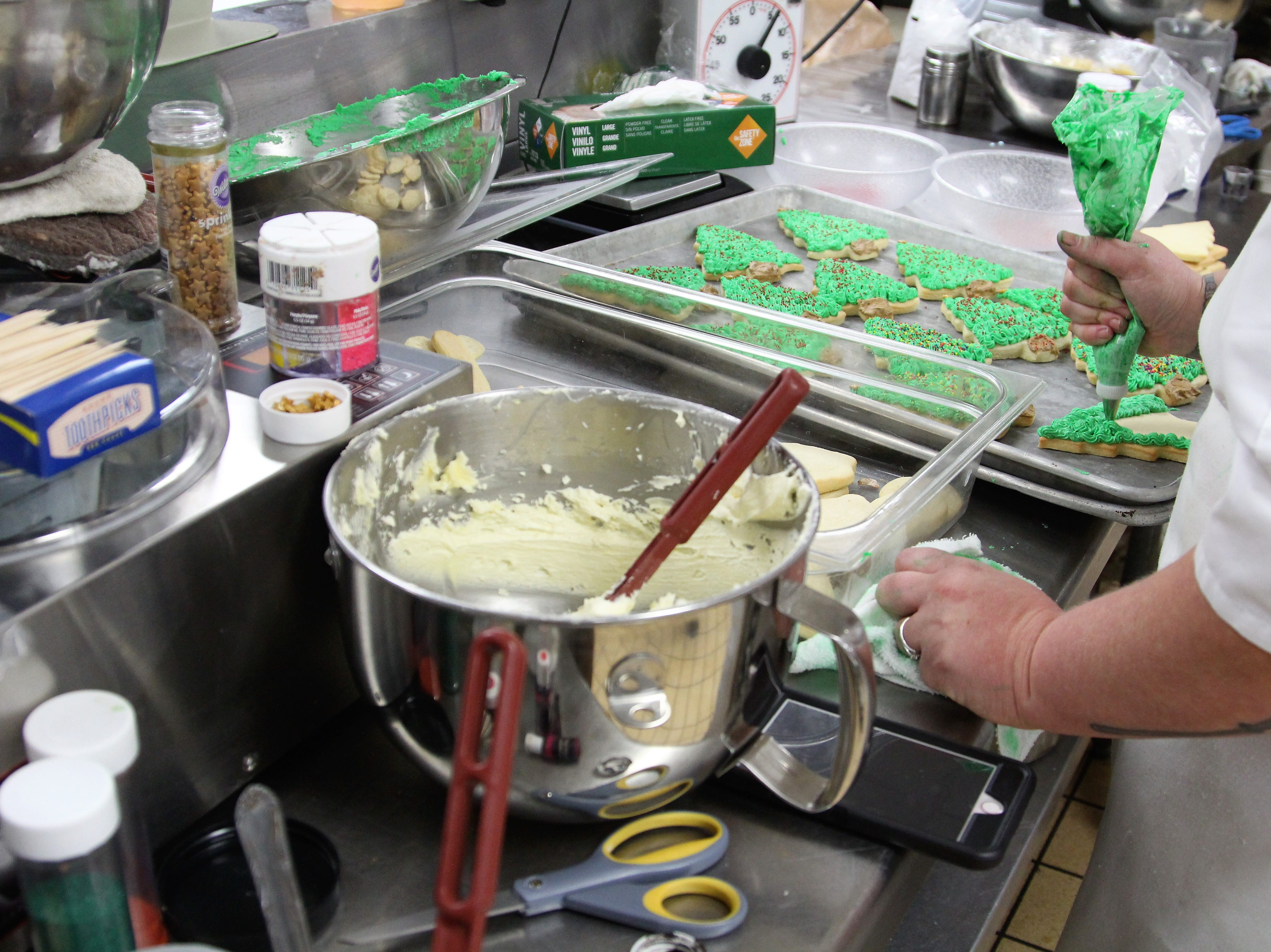 A culinary instructor at Tri-Rivers applies frosting on a batch of cookies Thursday morning. Students from high schools in Marion, Morrow and Union counties stopped by the kitchen, helping bake cookies and make pizzas from scratch.