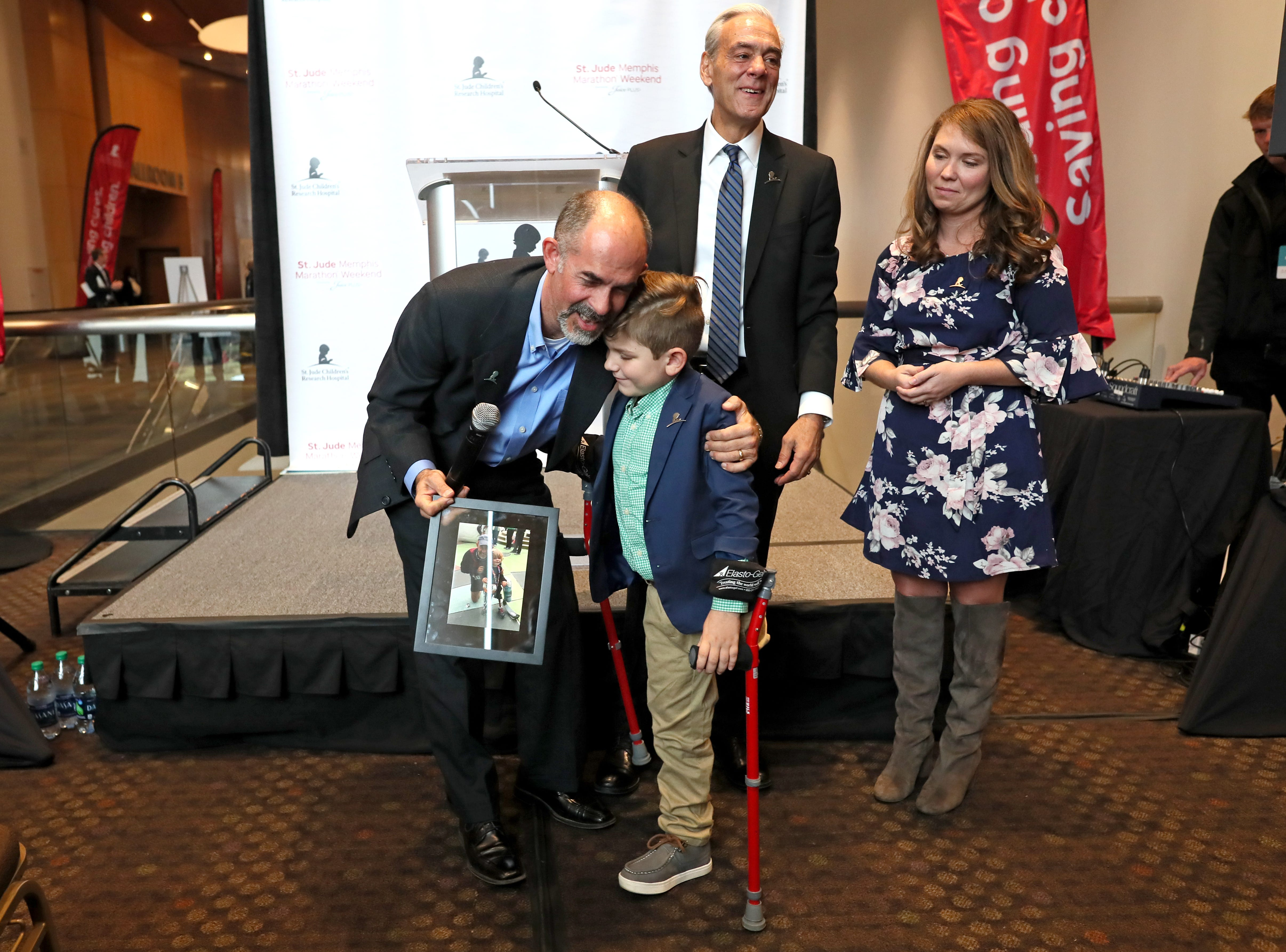 St. Jude Hero Among Us award recipient Kent Stoneking hugs Kael Hill, 6, during a press conference at the Cook Convention Center on Thursday, Nov. 29, 2018. Stoneking, who lost his leg in a motorcycle accident, has been an ambassador for St. Jude, running in their annual marathon to help children like Kael, who was a patient at the children's hospital.
