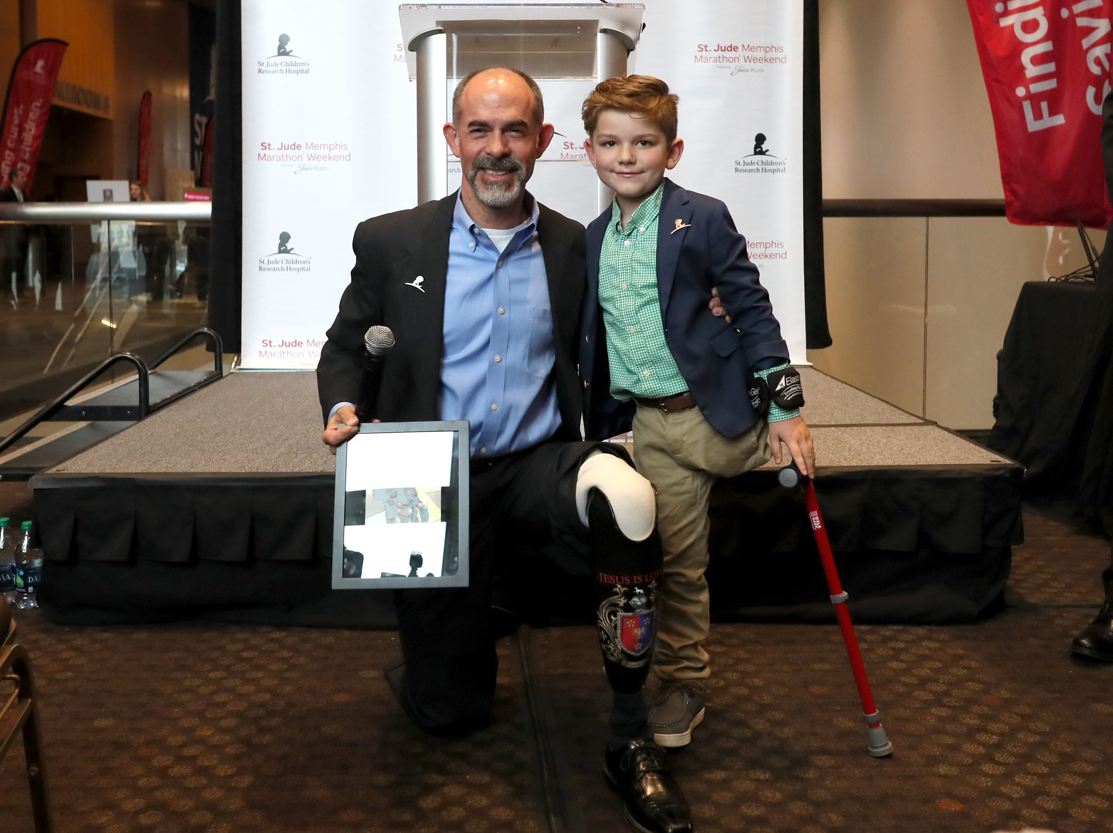 St. Jude Hero Among Us award recipient Kent Stoneking poses for a portrait with Kael Hill, 6, during a press conference at the Cook Convention Center Thursday, Nov. 29, 2018.