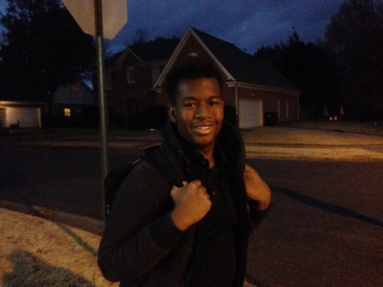 Musa Thomas, 15, a freshman at Collierville High School waits at 6:20 a.m. Thursday for the bus to school.