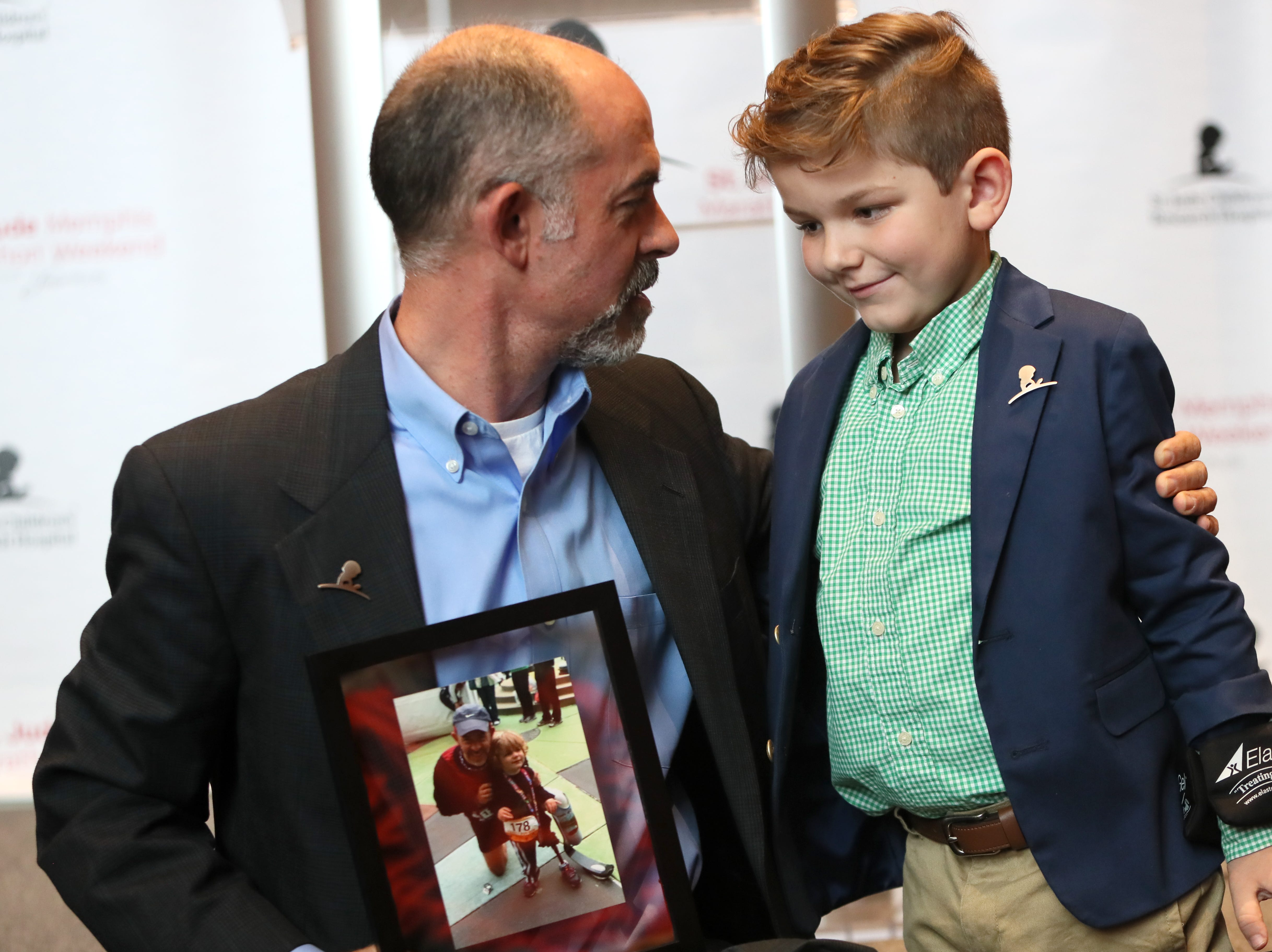 St. Jude Hero Among Us award recipient Kent Stoneking embraces Kael Hill, 6, during a press conference at the Cook Convention Center Thursday, Nov. 29, 2018.