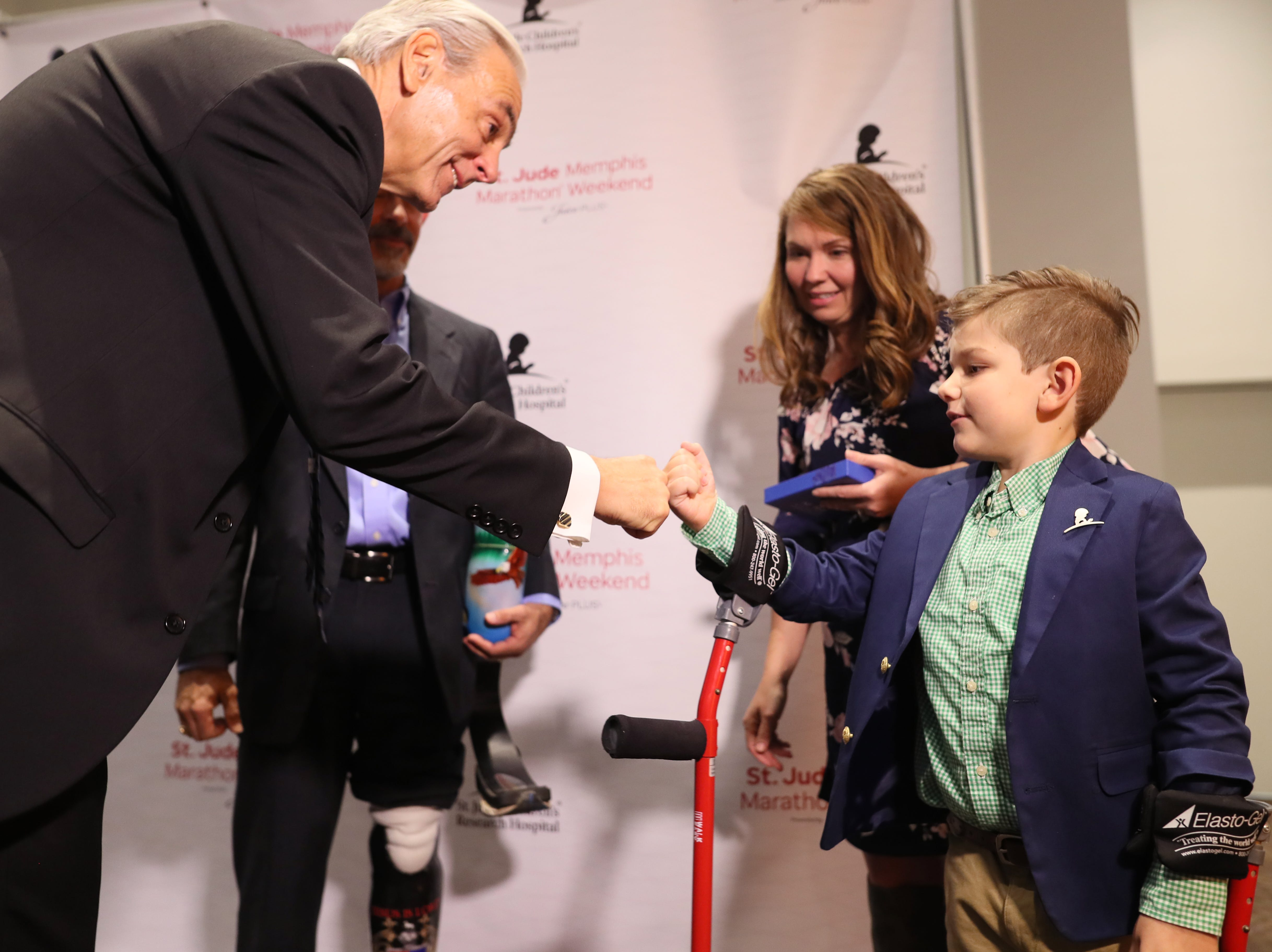 ALSAC President and CEO Rick Shadyac fist bumps Kael Hill, 6, during a press conference for the St. Jude Hero Among Us award at the Cook Convention Center on Thursday, Nov. 29, 2018.