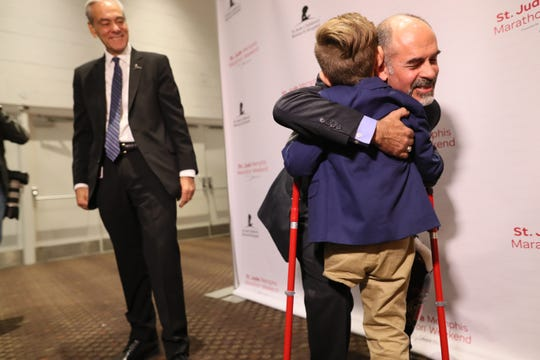 St. Jude Hero Among Us award recipient Kent Stoneking hugs Kael Hill, 6, as ALSAC President and CEO Rick Shadyac looks on during a press conference at the Cook Convention Center on Thursday, Nov. 29, 2018. Stoneking, who lost his leg in a motorcycle accident, has been an ambassador for St. Jude, running in their annual marathon to help children like Kael, who was a patient at the children's hospital.