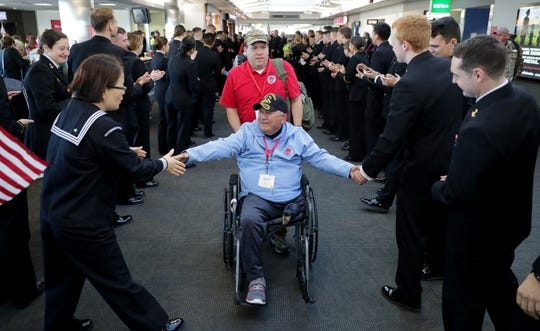 Vietnam veteran Ronald Tourtillott is greeted by Midshipman from the US Naval Academy in Annapolis with his guardian Rickey Tourtillott after getting off the plane in Baltimore Maryland before heading to Washington D.C. Some 145 veterans flew on two chartered planes to Washington D.C. as part of the Stars and Stripes Honor Flight.