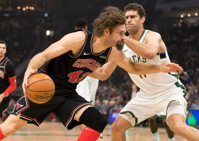 Bucks center Brook Lopez tries to prevent his twin brother Robin Lopez of the Bulls from driving to the basket on Wednesday night.
