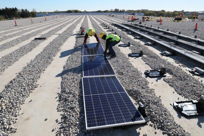 Workers ready solar panels for connection during the installation by Arch Electric at Lakeland Supply Inc. in Pewaukee.