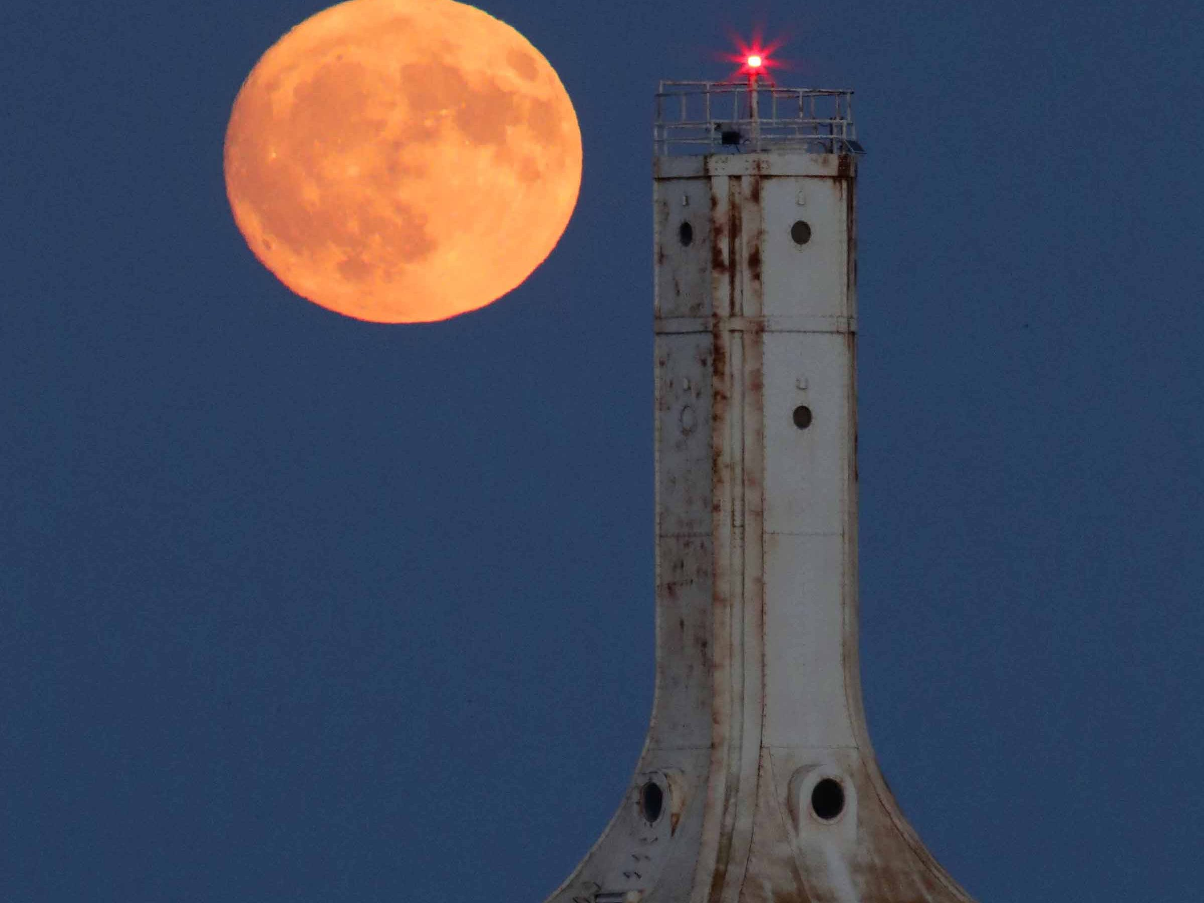 A nearly full waxing gibbous moon, at 99.4% full, rises over Lake Michigan behind the Port Washington breakwater light lighthouse on Oct. 23.