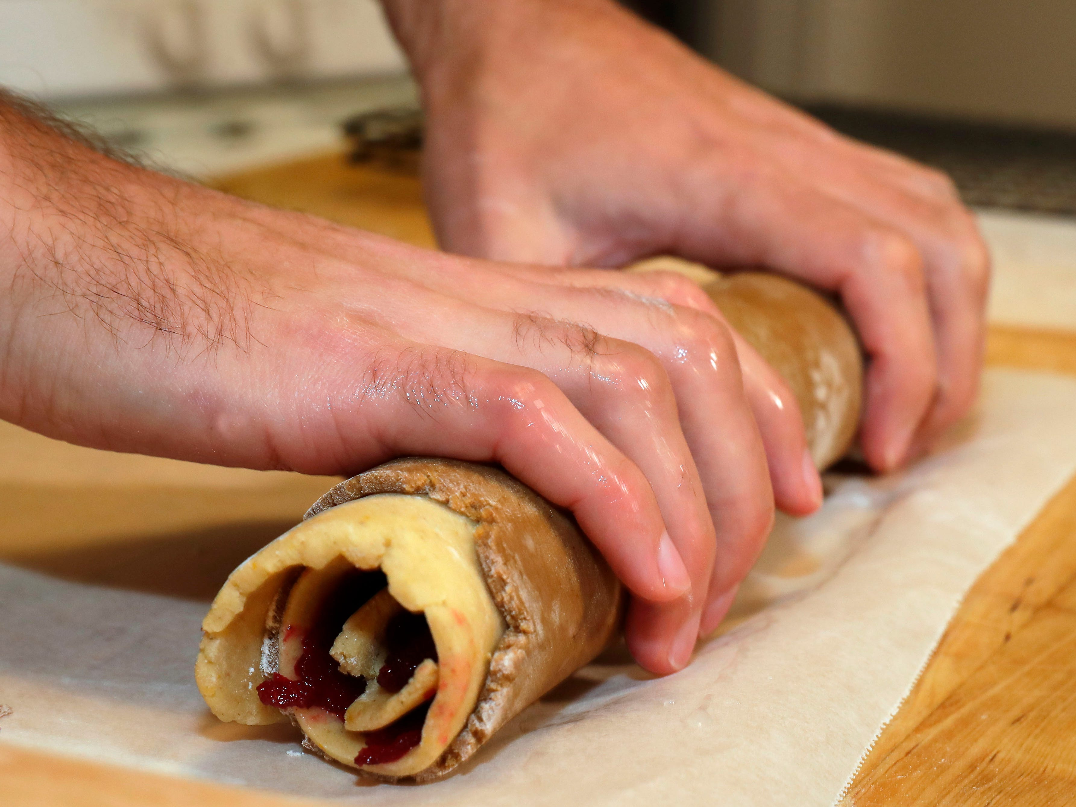 Behringer shapes the roll to help the layers adhere before putting it in the freezer.