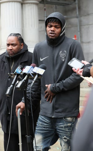 Press conference in front of Federal Courthouse in Milwaukee where Daniel Storm (not shown) an investigator announced he is presenting the U.S. Attorney with a request to investigate the case of Jerry Smith age 20 (right ) who was shot by Milwaukee Police officers, who thought he was going for a weapon.  At left is Tory Lowe a community activist.  Here Smith describes the lasting effect of his shooting injury.