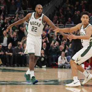 Bucks forward Khris Middleton (22)  is congratulated by teammate Malcolm Brogdon after hitting the game-winning three-pointer against the Bulls with 5.2 seconds left on Wednesday night.