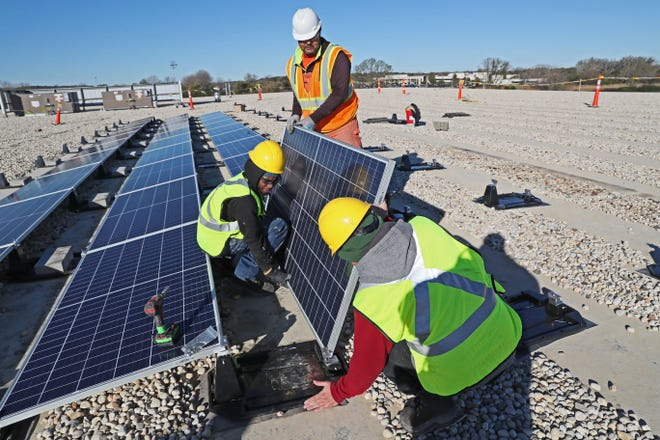 Arch Electric employees Octavio Garduno (foreground) Branden Fitzhugh (left) and Ruben Zamora install solar panels in 2018. The company plans to install solar panels on the roof of the Whitefish Bay Public Works Department this summer.
