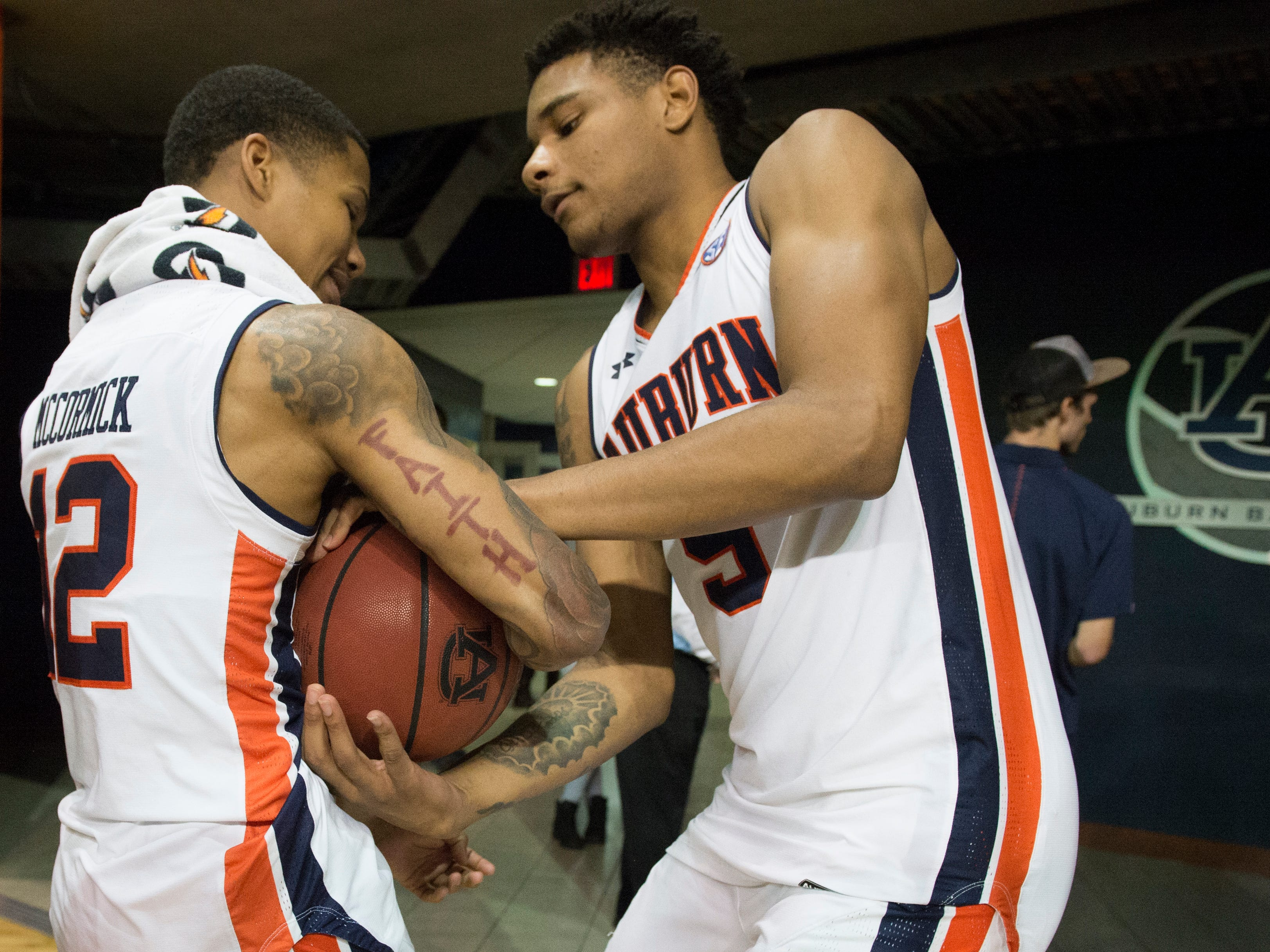 Auburn guard J'Von McCormick (12) and Chuma Okeke (5) fight over a ball as they walk off the court at Auburn Arena in Auburn, Ala., on Wednesday, Nov. 28, 2018. Auburn defeated Saint Peter's 99-49.