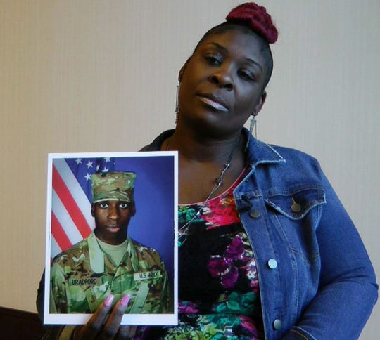 "In this still image taken from video, April Pipkins holds a photograph of her deceased son, Emantic ""EJ"" Bradford Jr. Bradford was shot to death by a police officer in a shopping mall on Thanksgiving night."