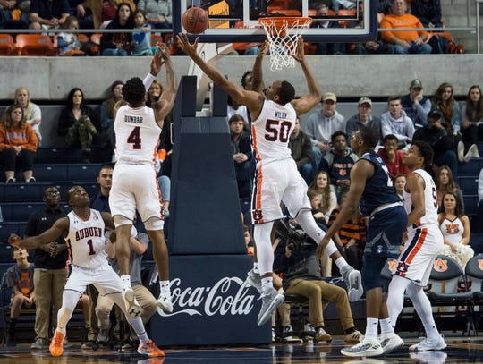 Auburn guard Malik Dunbar (4) and Auburn center Austin Wiley (50) jump for a rebound at Auburn Arena in Auburn, Ala., on Wednesday, Nov. 28, 2018. Auburn defeated Saint Peter's 99-49.