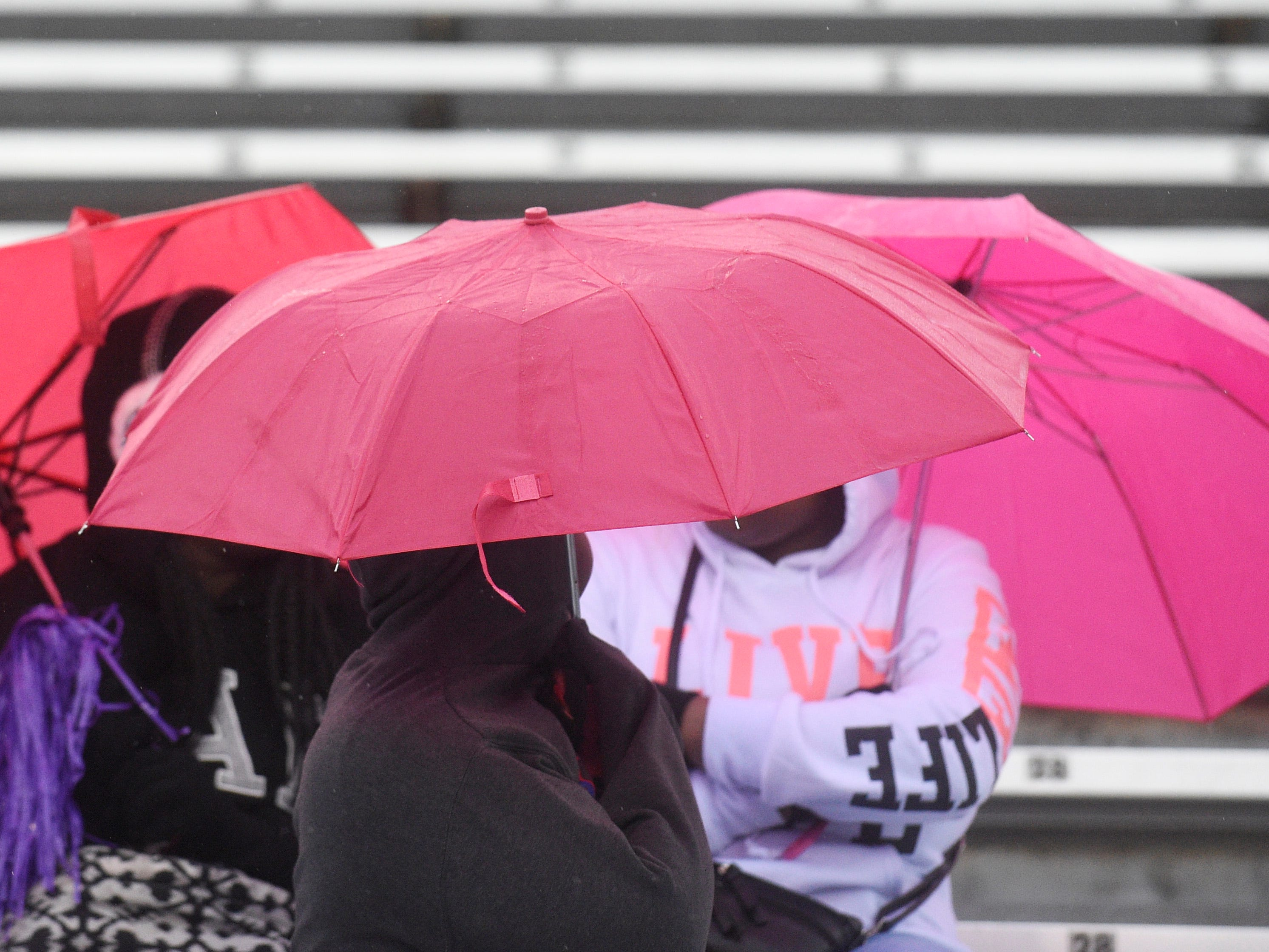 Fans huddle under umbrellas before the Class 4A BlueCross Bowl state championship at Tennessee Tech's Tucker Stadium in Cookeville, Tenn., on Thursday, Nov. 29, 2018.