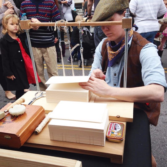 Mary Louise Sullivan of Crowing Hens Bindery demonstrates bookbinding at the 2017 Dickens of a Christmas.
