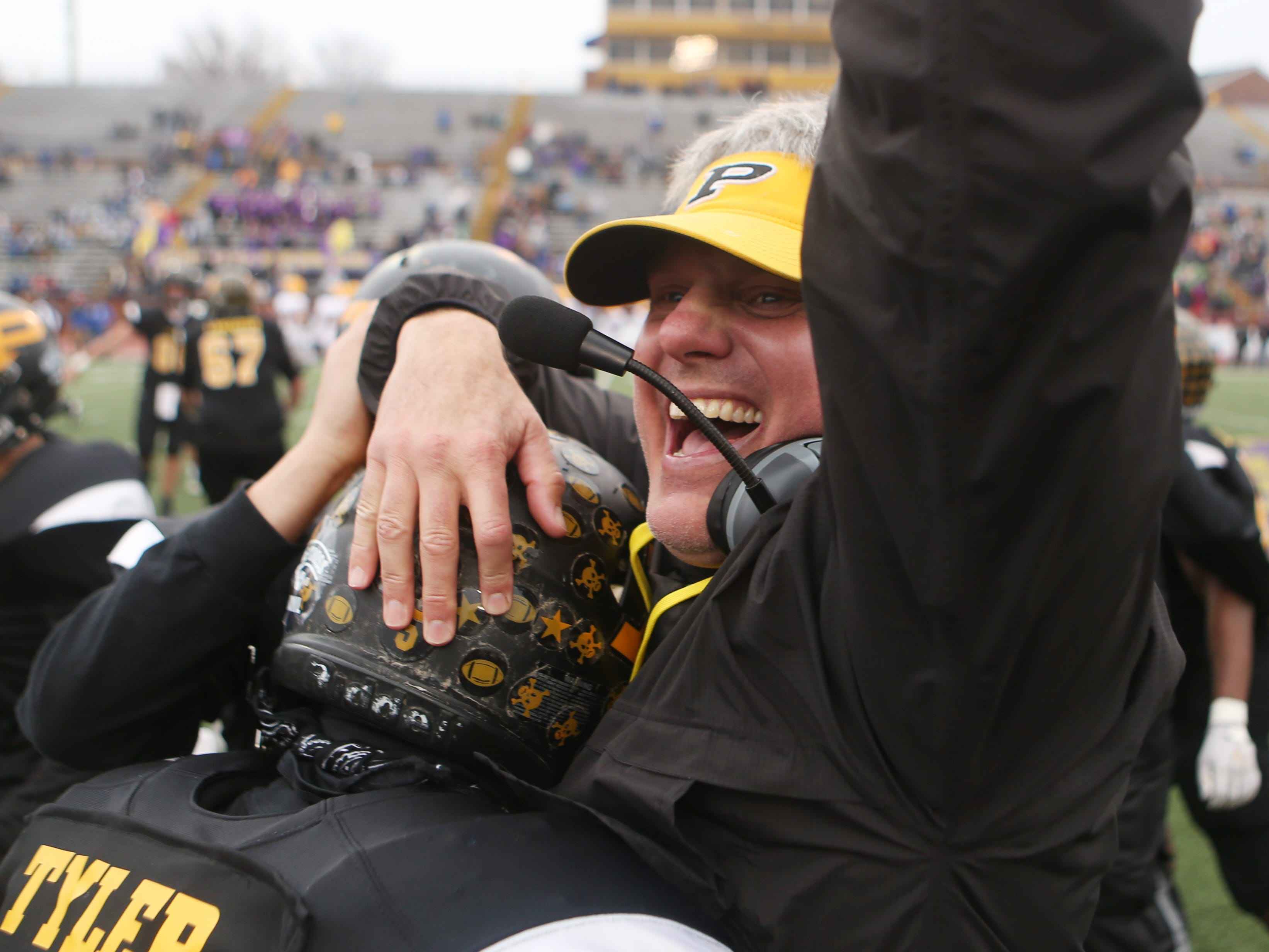 Peabody assistant coach Tab Vowell celebrates the team's win with Desmond Tyler (5) in the Class 2A BlueCross Bowl state championship at Tennessee Tech's Tucker Stadium in Cookeville, Tenn., on Thursday, Nov. 29, 2018.