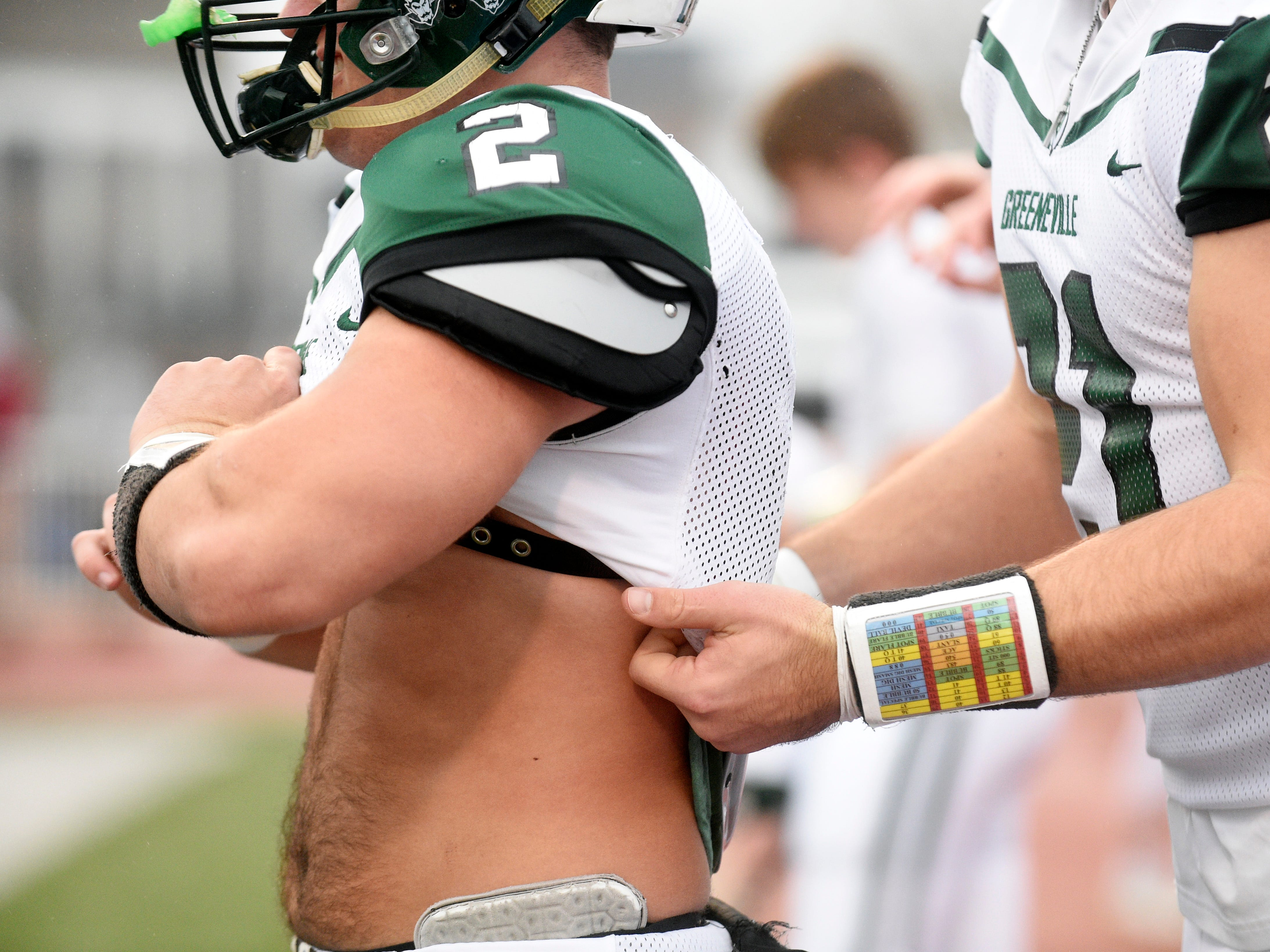 Greeneville's Jaevon Gillespie (20)  helps teammate Cade Ballard (2) get ready for the Class 4A BlueCross Bowl state championship at Tennessee Tech's Tucker Stadium in Cookeville, Tenn., on Thursday, Nov. 29, 2018.