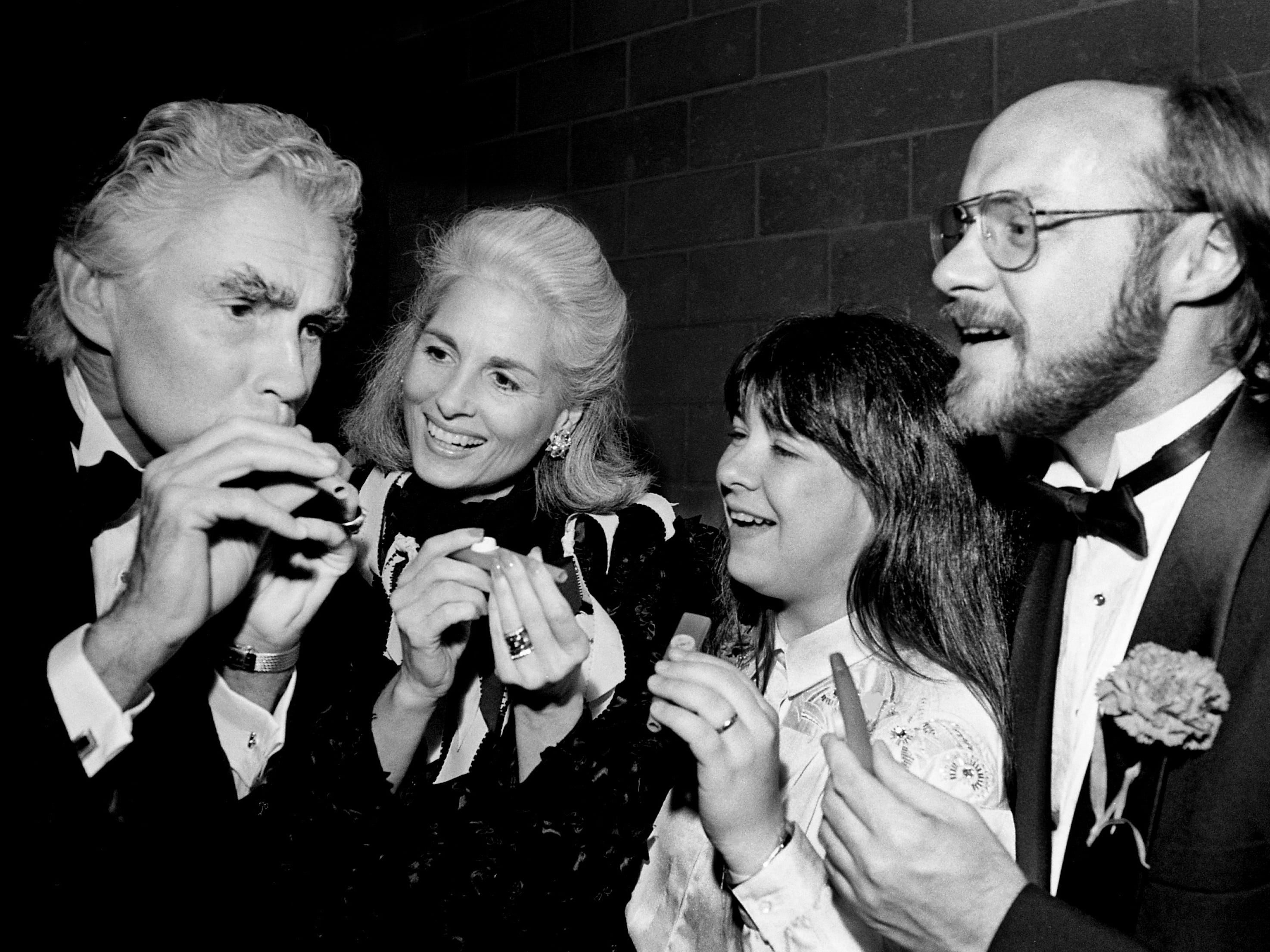 """Audience members at the first performance of the Nashville Symphony's new season Nov. 4, 1988, got a chance to make music of their own with kazoos during the high-spirited finale, """"Stars and Stripes Forever."""" Symphony conductor Kenneth Schermerhorn, left, gives a demonstration to his wife, Tish, concert mistress Teresa Fream and assistant conductor Brian Groner."""