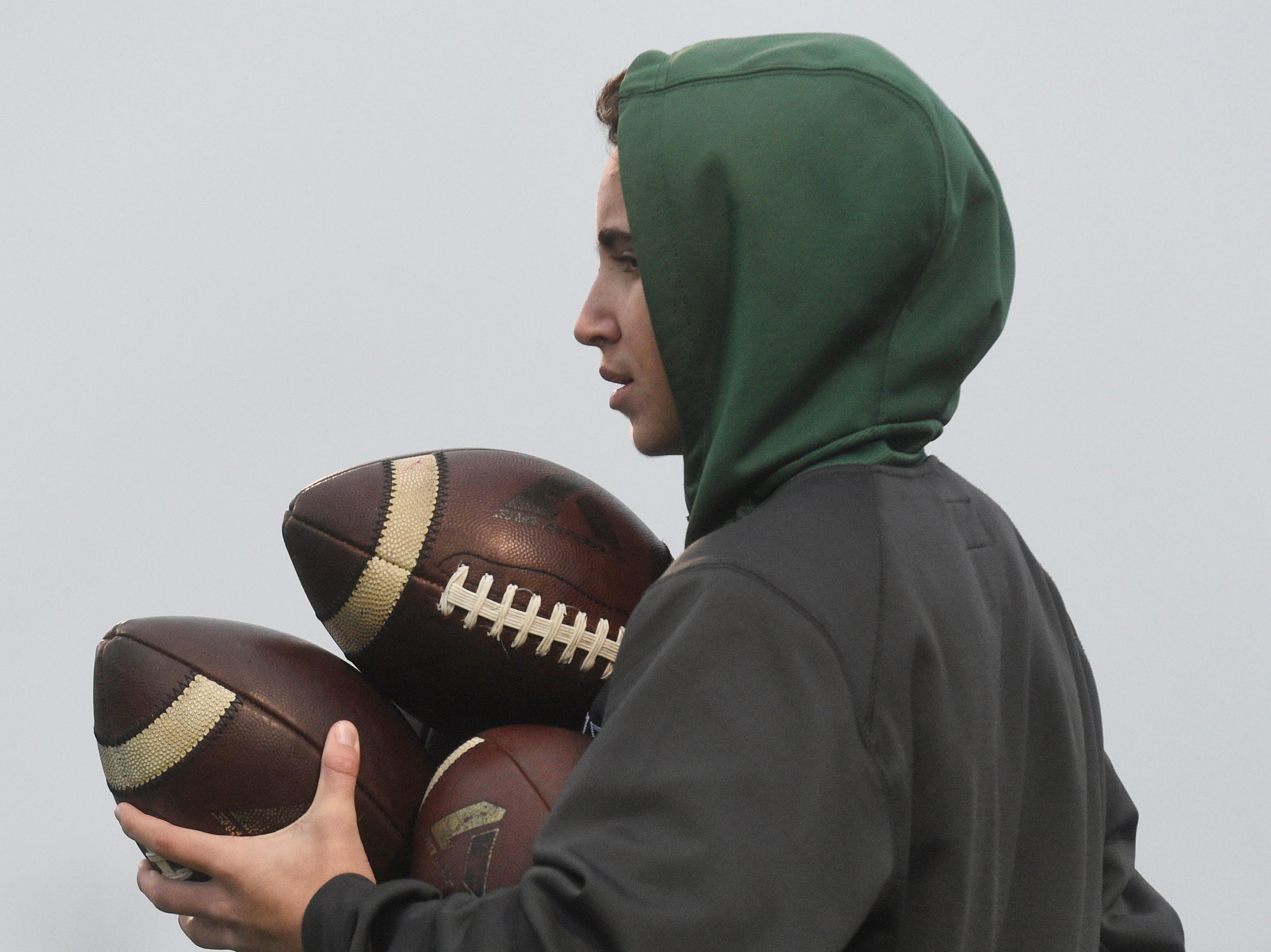 A Greeneville ball boy carries several balls before the Class 4A BlueCross Bowl state championship at Tennessee Tech's Tucker Stadium in Cookeville, Tenn., on Thursday, Nov. 29, 2018.