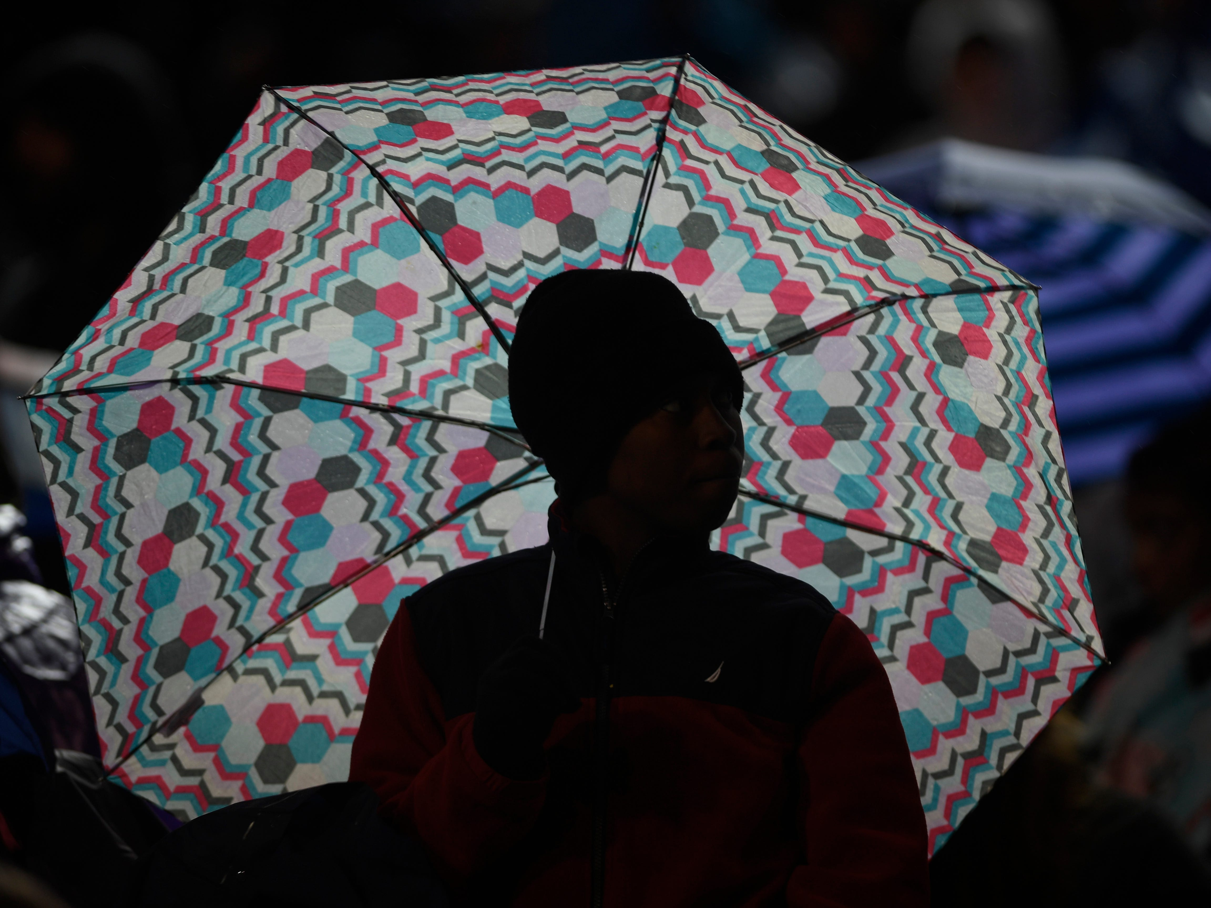 A fan is silhoetted under an umbrealla during the Class 4A BlueCross Bowl state championship at Tennessee Tech's Tucker Stadium in Cookeville, Tenn., on Thursday, Nov. 29, 2018.