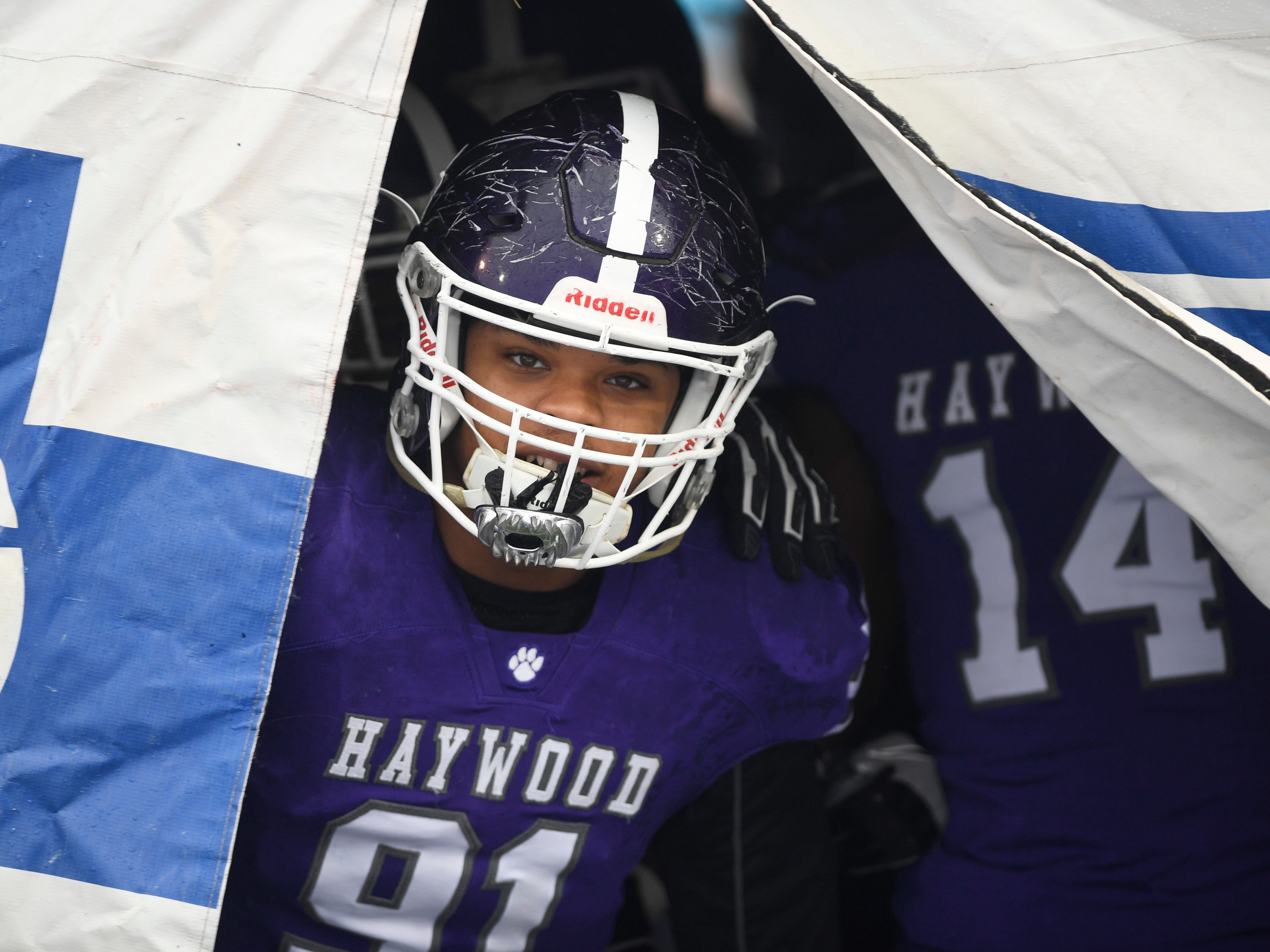 Haywood's  Jewin Young (91) peeks out from behind a banner before taking the field for the the Class 4A BlueCross Bowl state championship at Tennessee Tech's Tucker Stadium in Cookeville, Tenn., on Thursday, Nov. 29, 2018.