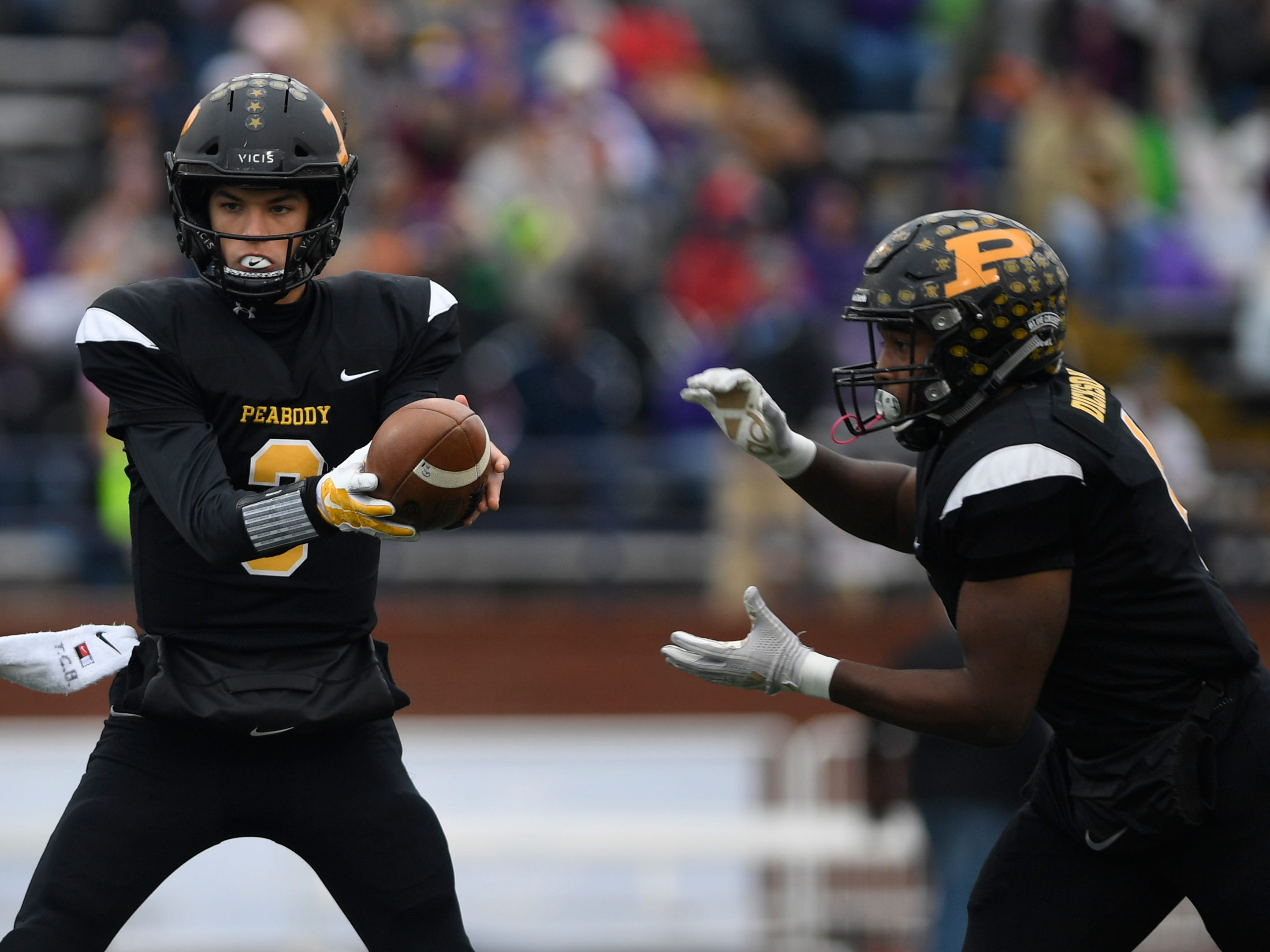 Peabody quarterback Cooper Baugus hands off to running back Jarel Dickson in the first quarter during the Class 2A BlueCross Bowl state championship at Tennessee Tech's Tucker Stadium in Cookeville, Tenn., on Thursday, Nov. 29, 2018.