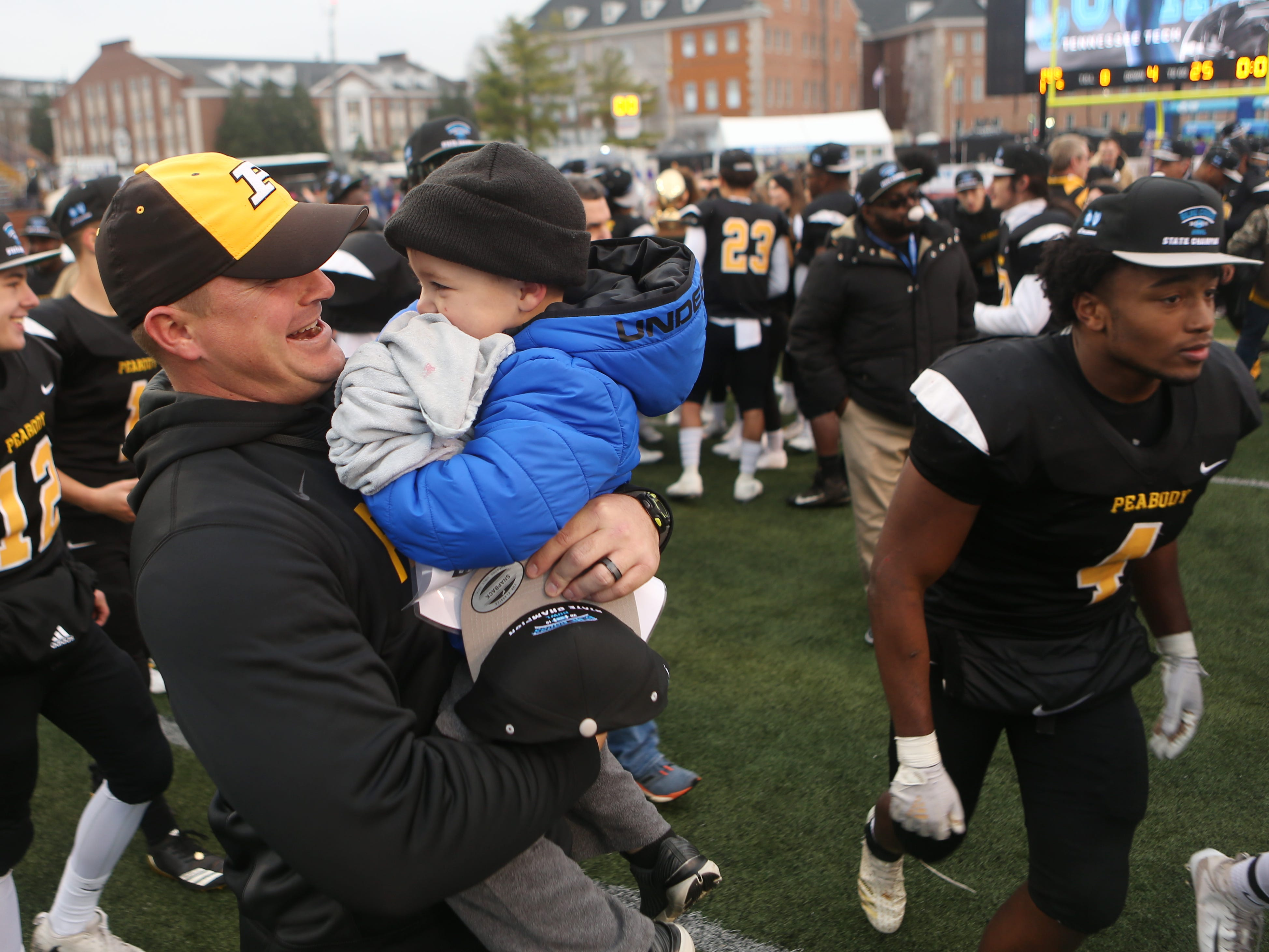 Peabody's head coach Shane Jacobs hugs his son Nolan after his team's win over Trousdale County in the Class 2A BlueCross Bowl state championship at Tennessee Tech's Tucker Stadium in Cookeville, Tenn., on Thursday, Nov. 29, 2018.