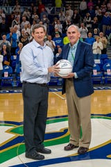 FGCU women's basketball coach Karl Smesko is presented a basketball by athletic director Ken Kavanagh commemorating his 500th victory prior to the Eagles' game against Houston on Wednesday, Nov. 28, 2018. Smesko got his 500th win on Sunday, Nov. 25 against American University.