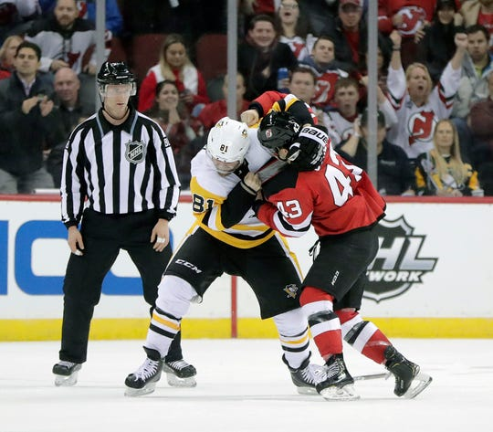 Pittsburgh Penguins right wing Phil Kessel (81) and New Jersey Devils left wing Brett Seney (43) fight during the second period of an NHL hockey game, Tuesday, Nov. 13, 2018, in Newark, N.J.