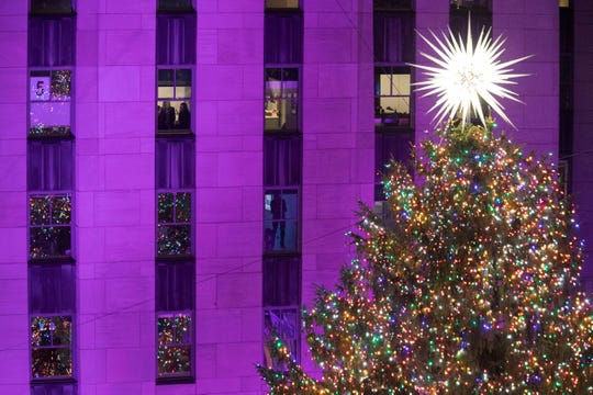 People watch as the Rockefeller Center Christmas tree is lit during the 86th annual Rockefeller Center Christmas tree lighting ceremony, Wednesday, Nov. 28, 2018, in New York.