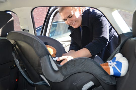Luna County Parents as Teachers Director Anna Barraza shows how to install a child car seat.