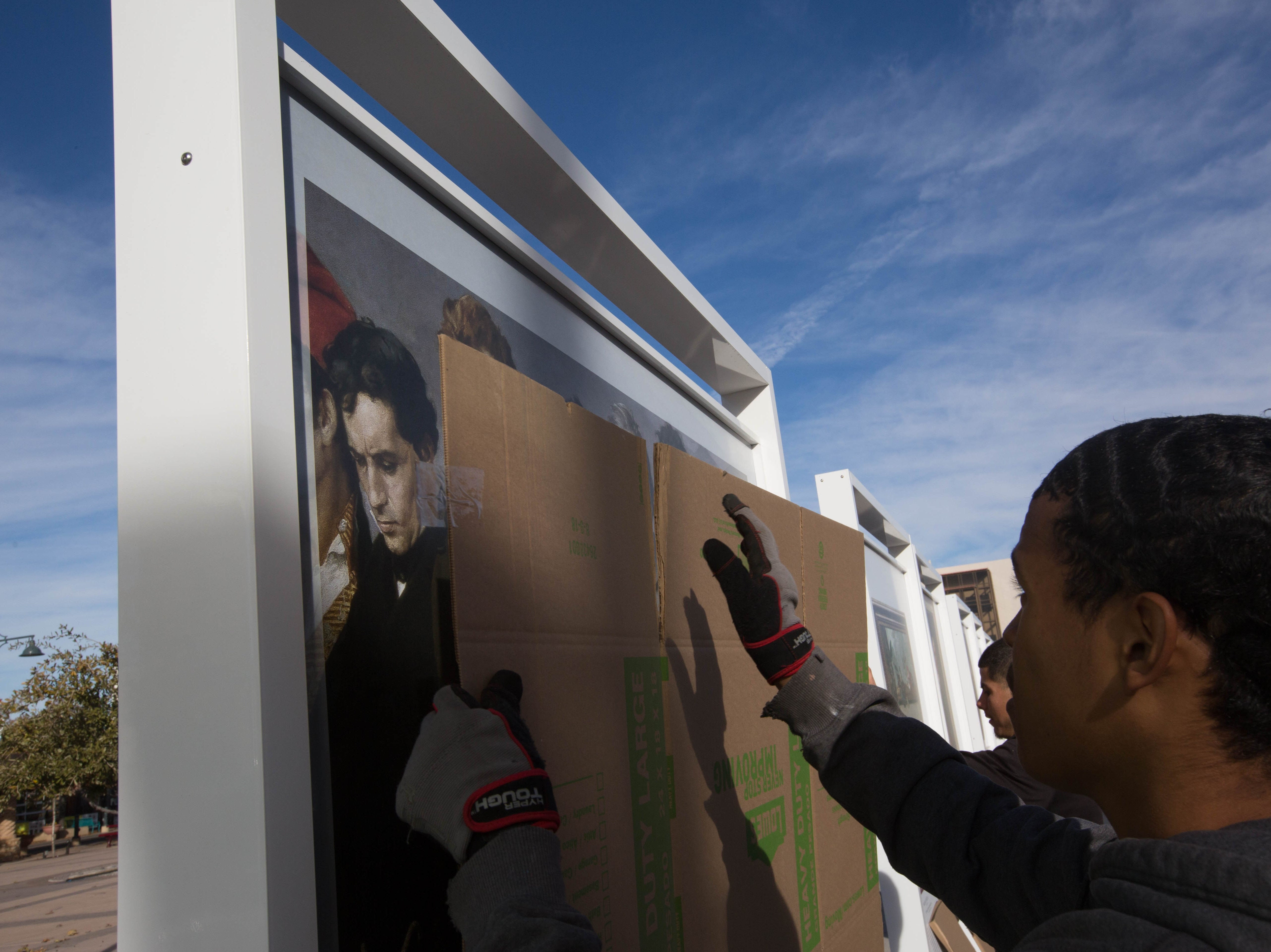 "Joseph Allen, left, and Phillip Garcia, right, place cardboard over a replica painting of Antonio Gisbert's ""The Execution of Torrijos and his Companions on the Beach at Málaga"" as ""The Prado in Las Cruces"" exhibit is packed up ending its three month stay in the Plaza de Las Cruces, Thursday November 29, 2018."
