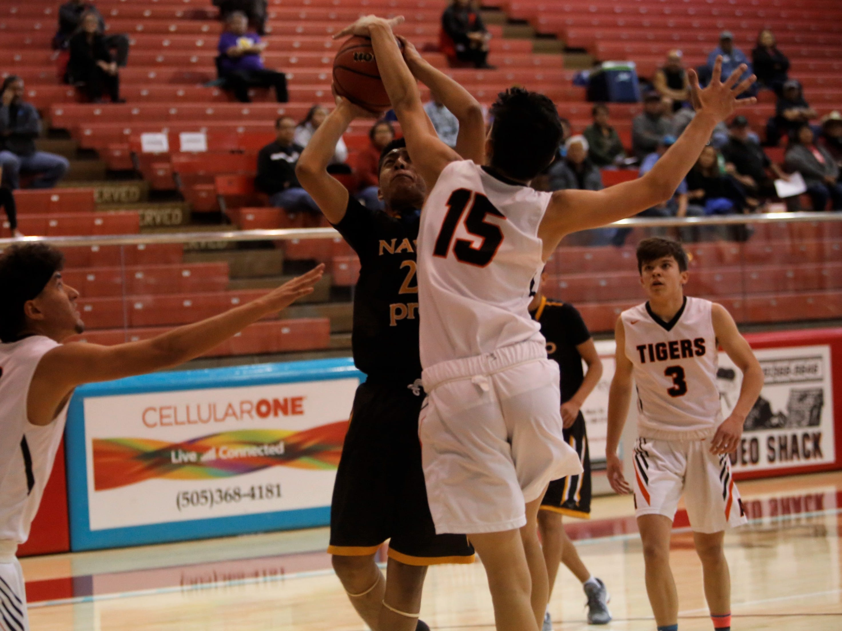 Navajo Prep's Treston Yazzie draws contact under the basket against Aztec's Austin Schaub (15) during the Jerry Richardson Memorial tournament Thursday at Shiprock.