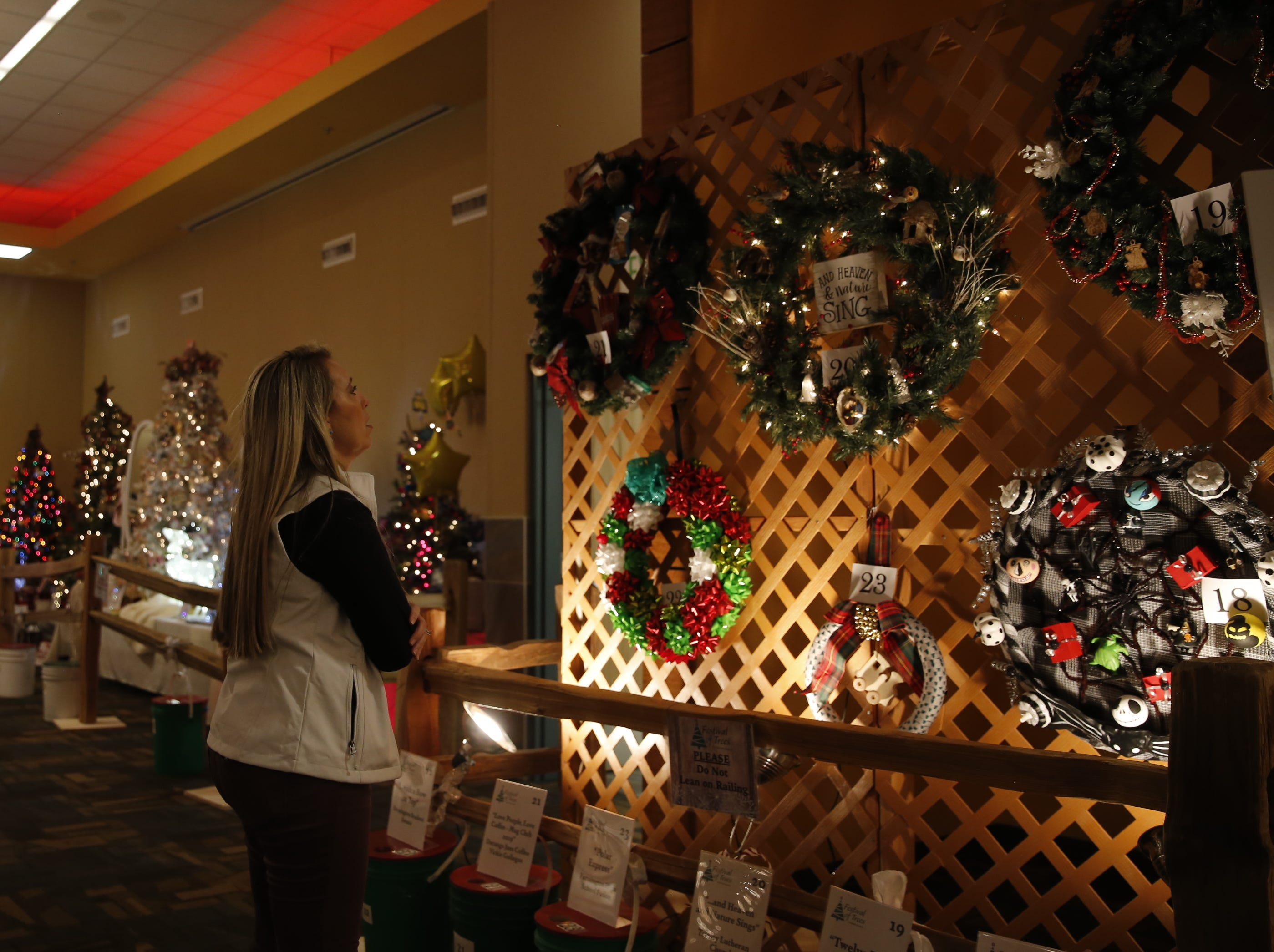 Hazel Jackson looks at wreaths displayed, Wednesday, Nov. 28, 2018, during Festival of Trees at the Farmington Civic Center.